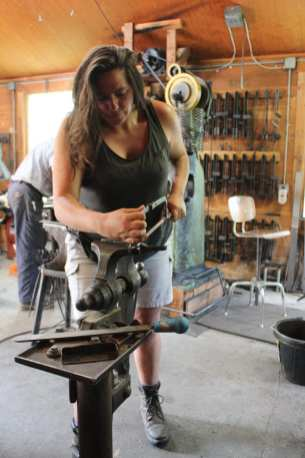 A young woman trims a blade to size in the blacksmithing class