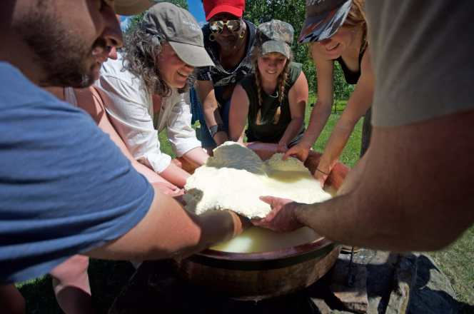 photo of many students surrounding a copper kettle filled with milk and extracting cheese from it