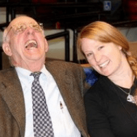 photo of Leah bayens sitting and laughing with Wendell Berry in a classroom with lots of chairs