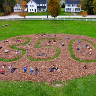 Students lay in the middle of a giant 350.org symbol raked together out of leaves that fell on Craftsbury Common