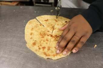 Naan Bread being cut in several pieces to share with the community for the celebration of Diwali.