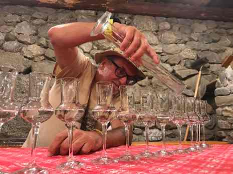 a man wearing glasses and a hat pours schnapps into a line of delicate stemmed glasses