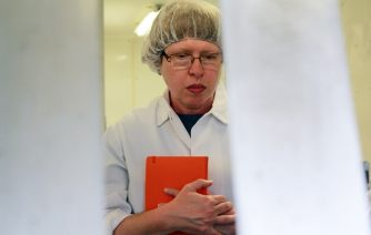 a woman wearing glasses, a hairnet, and a white coat holding a red notebook