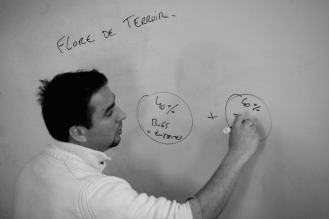 a black and white photo of a man writing on a whiteboard