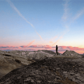 Person standing alone on mountain top. Other peaks nearby. Low pink clouds on horizon and pink streaks set on blue sky background.