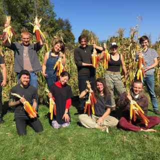 10 students holding native corn in front of heritage garden on sunny fall day.
