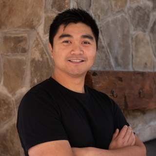 Will Casela, Director of Video & Audio Production, smiles. He stands with his arms crossed in front of a flagstone wall.