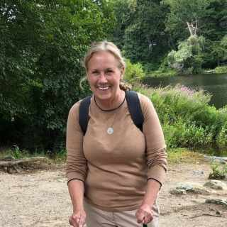 Debbie is wearing a long-sleeved brown shirt and wearing a backpack. She is standing along a river.