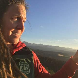 Erin is wearing a US Forest Service vest over a red shirt and is pointing to a distant mountain range