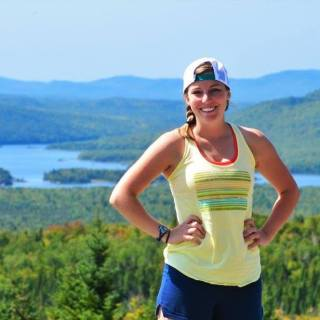 Molly is wearing a yellow tanktop, blue shorts, and a baseball cap on backwards. She is standing at the top of a mountain with water and hills behind her.