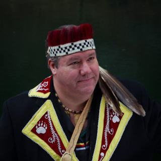 Chief Stevens is wearing traditional Abenaki attire against a dark gray background