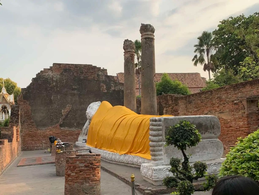 Reclining Buddha draped in saffron colored robe