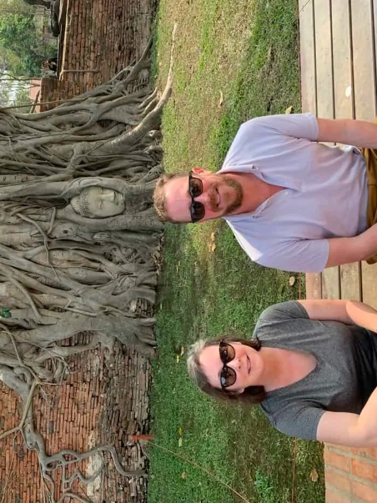 Steve and Noelle sitting at the Buddha head in a tree