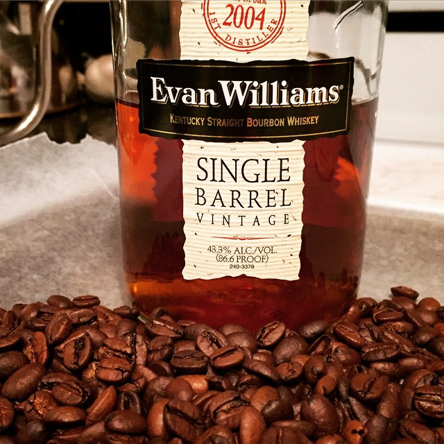 Freshly-roasted, bourbon-infused coffee on a cooling tray in front of a bottle of Evan Williams Single Barrel Bourbon