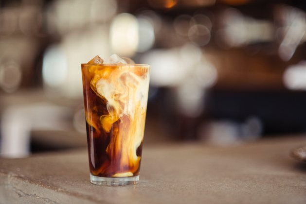 A glass of cold-brew coffee, served over ice, with a swirl of cream.