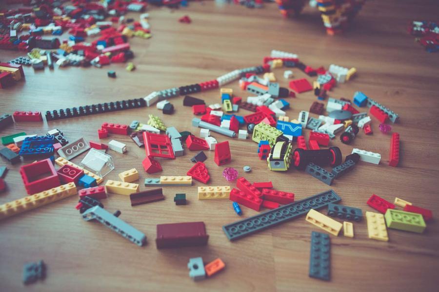 A pile of LEGO bricks spread out across a hardwood floor