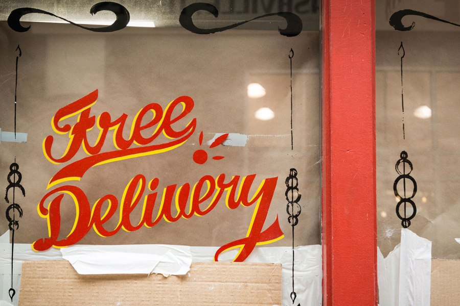 """Free Delivery"" written in a script font on a restaurant window"