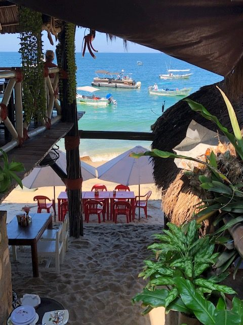 Looking down to the beach tables from inside the restaurant. Tables are nicely framed by the building on left and right, a sand floor, and small boats close to shore in the background.