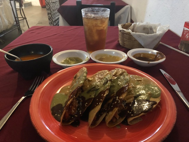4 tacos, all 3 moles covering them