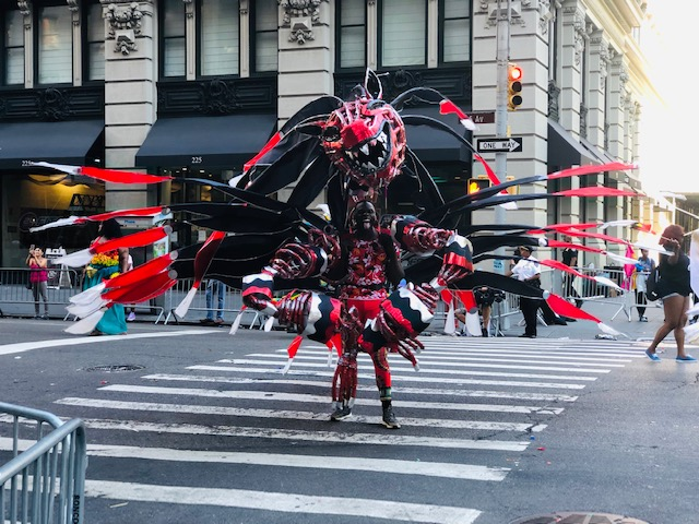 A black guy in an amazing and huge costume, a crosss between a dragon and giant insect due to the type of wings; all in black and red