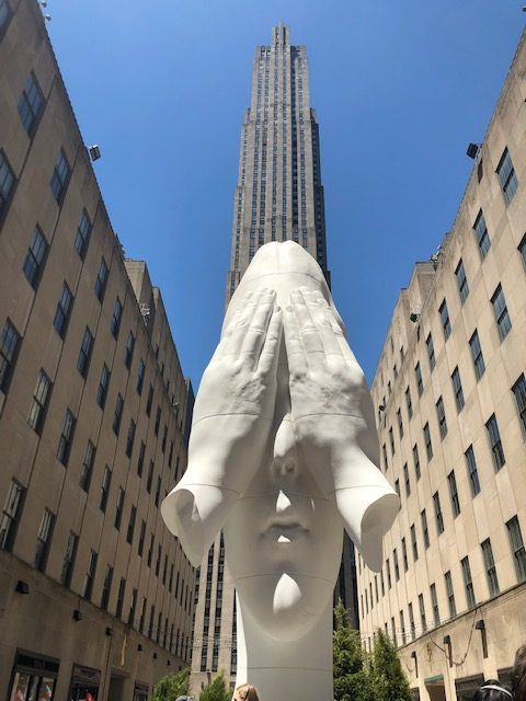 A 21 foot high sculpture of a girl's face with her hands - just hands, no arms - over her eyes, with Rockefeller Center behind it