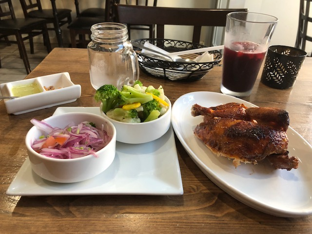 1/2 a chicken, steamed vegetables (broccoli, cauliflower, carrots, yellow zucchini) and an onion salad; with a juice drink in the background