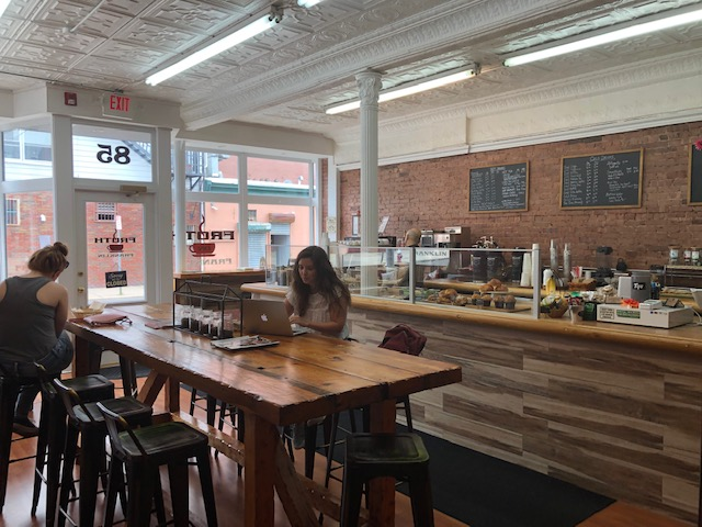 The main area of the cafe: a communal table in the middle seating about 8, the counter and cashier in the background, front door to the far left