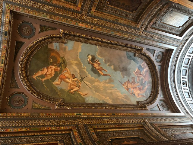 Ornate wood ceiling with a classical painting covering much of the center