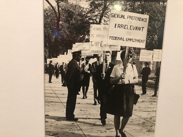"""Photo from the 60s: conservatively dressed people carrying protest signs. The one in front says """"sexual preference is irrelevant to federal employment"""""""