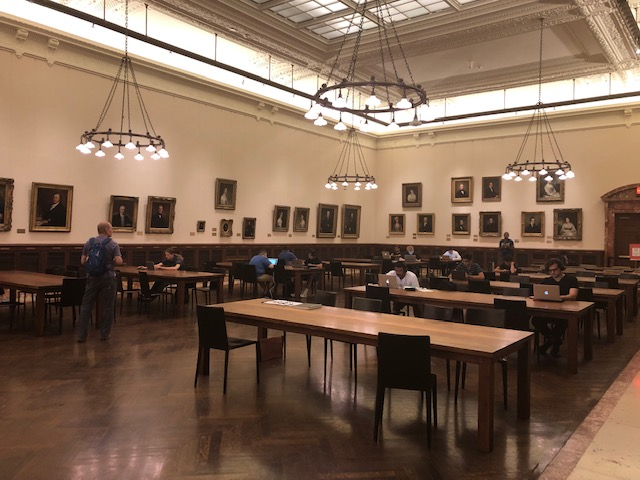 A huge room with long tables, people scattered throughout mostly working on laptops, walls covered in old painted portraits
