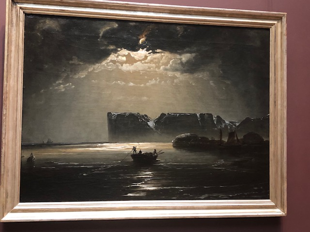 Oil on canvas in white, black, and shades of gray. A small boat in the water with 3 men in it, moonlight coming through ominous clouds above them, big rocks in the water in the background