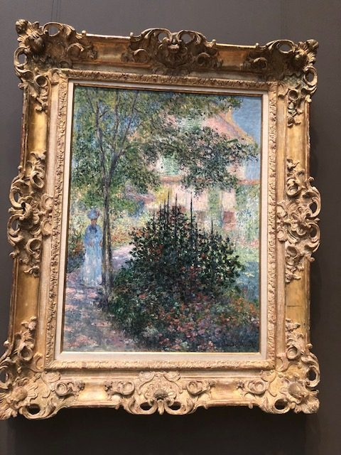 Impressionist style paitning, a woman standing under a tall tree, almost in the background, with a huge bush of hollycock in the foreground
