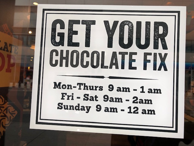 A sign with Get Your Chocolate Fix in the top half, store hours in the bottom half