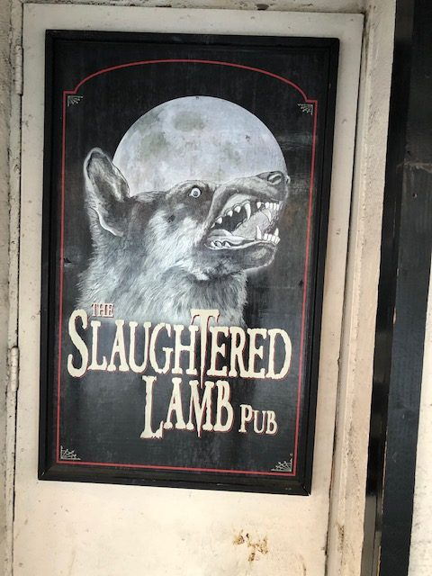 Poster at a place called The Slaughtered Lamb Pub, with a wolf's head against a bright moon