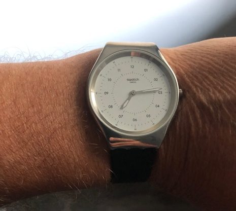 Simple silver watch with a white face, actual numbers for the clock