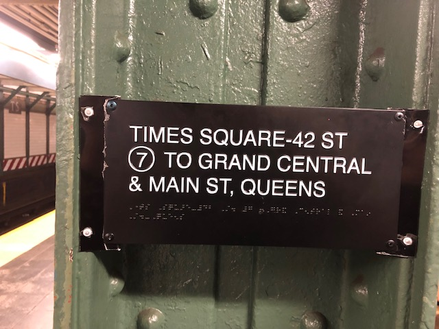 Small metal sign on a beam in the subway platform: Times Square 42 St, 7 to Grand Central & Main St, Queens. Also in Braille beneath it