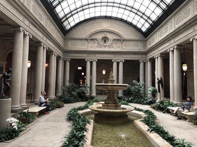 Atrium courtyard in the center. Columns along the edges, fountain in the middle, park benches, plants, statues