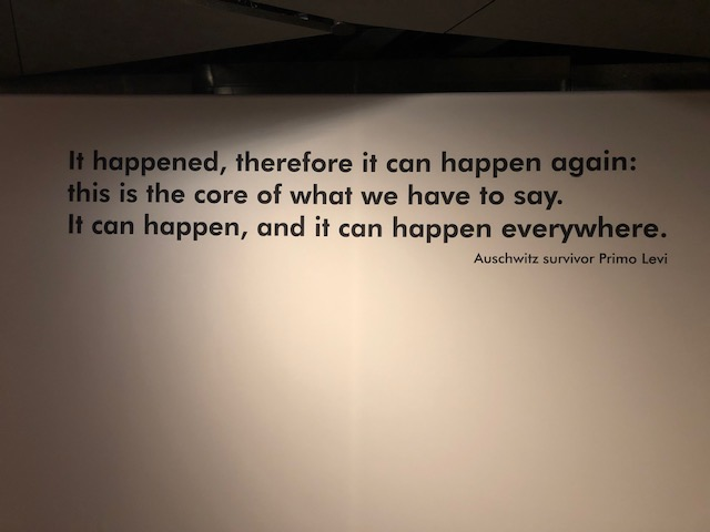 """quote on museum wall: It happened, therefore it can happen again: this is the core of what we have to say. It can happen, and it can happen everywhere."""" Auschwitz survivor Primo Levi"""