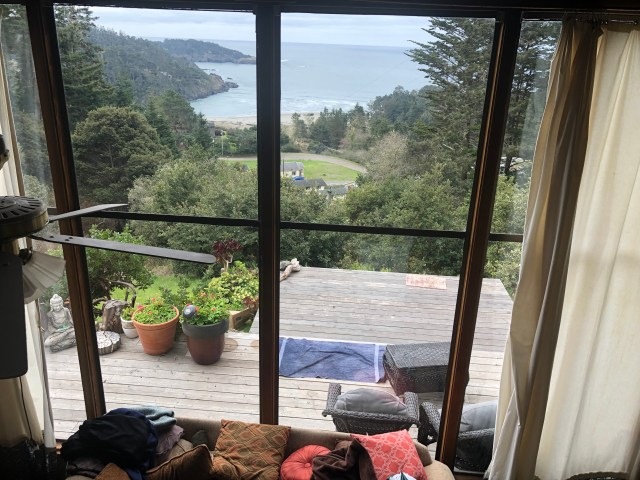 """an """"above"""" shot with the couch in front, the deck past the windows and the ocean beyond that"""