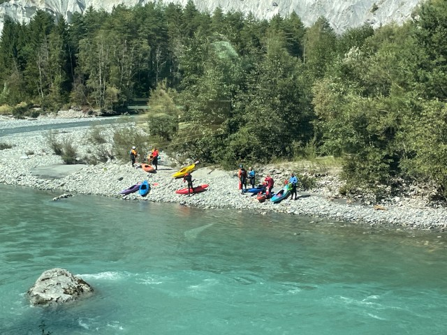 guys in kayaks on the beach of the river about to go in
