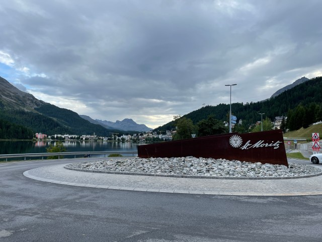 Decorative St Moritz sign in the middle of a roundabout next to the lake, with mountains and town in the background.