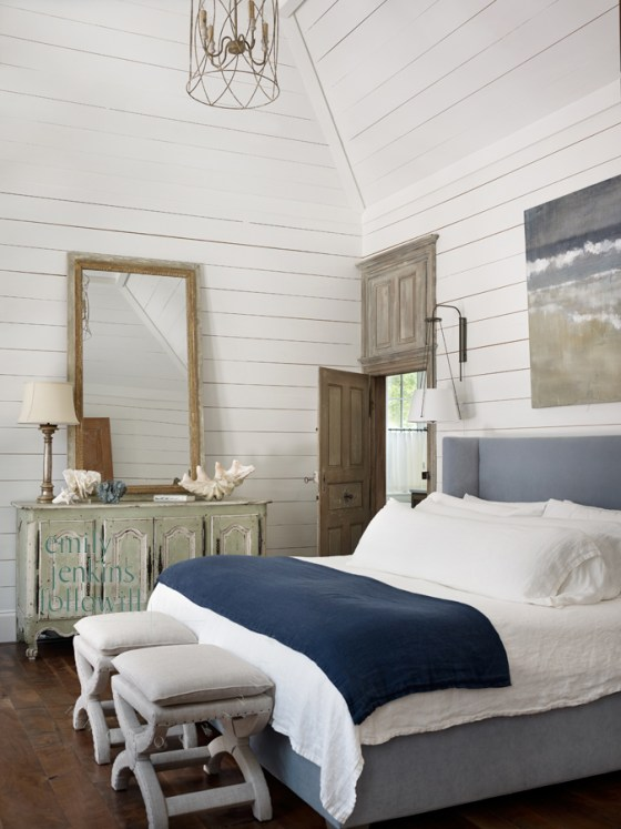 This master bedroom in a coastal cottage in Watercolor, Florida will be featured in Décor magazine. Rich pops of color and salvaged doors distinguish it from a typical beach-house look…nice work by Tim Adams. High ceilings don't feel too large, thanks to the wood-plank walls and large-scale furnishings. Photography: Emily Followill