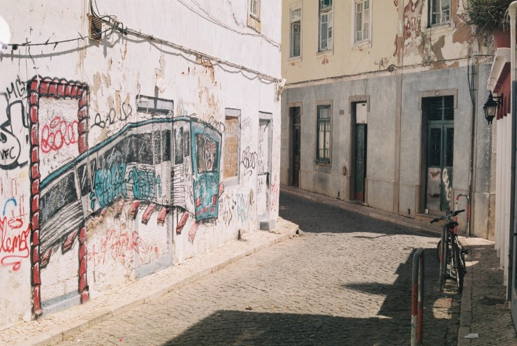 Analogue photo of a derelict cobbled Portuguese street with graffiti of a subway train travelling out through a door