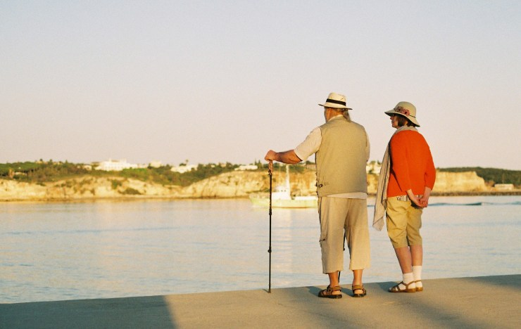 An elderly couple in summer clothes look out across the river