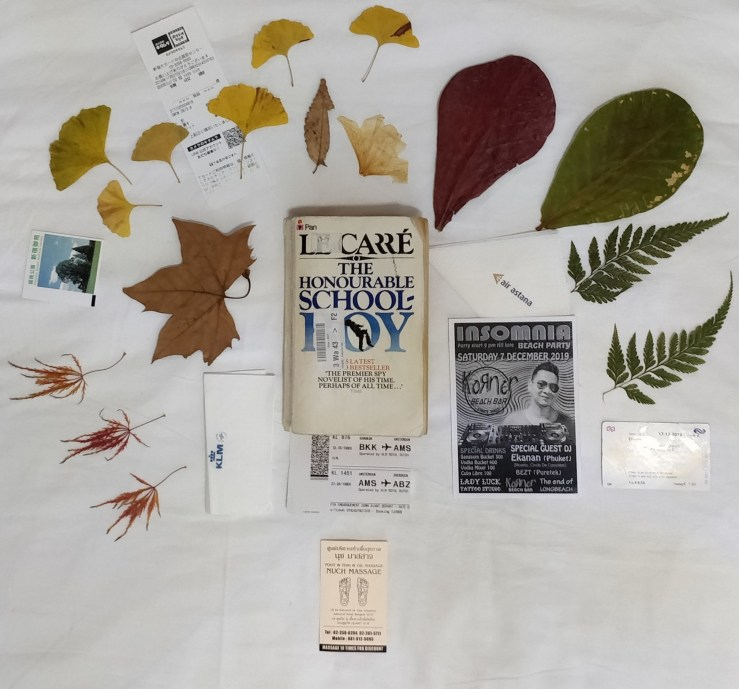 Photo of paperback copy of The Honourable Schoolboy by John le Carre surrounded by leaves collected during the reading.