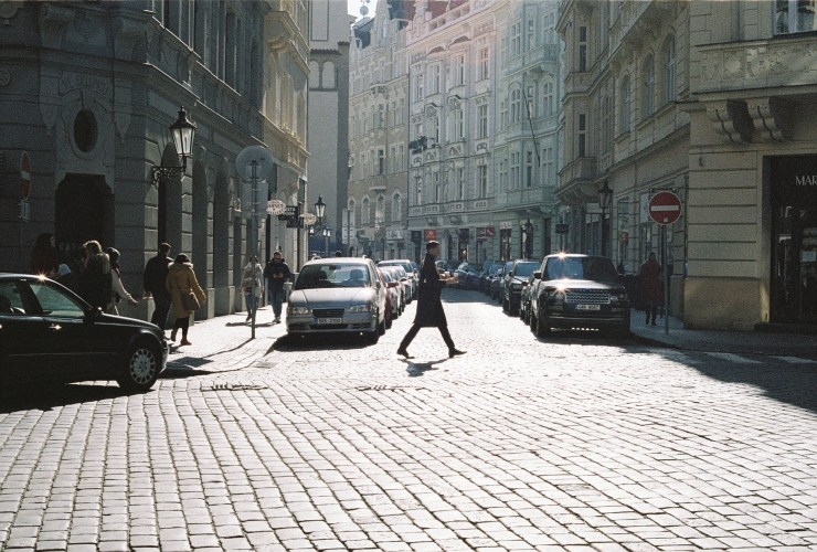 analogue photo of a man in a trench coat crossing a cobbled street in the sunshine holding two cups of coffee. Prague