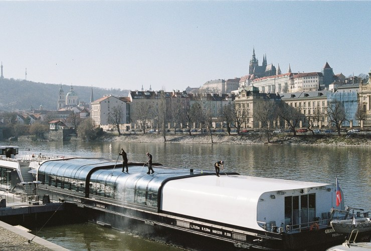 Analogue photo of men cleaning the windows of a barge on the Vltava River in front of Prague castle