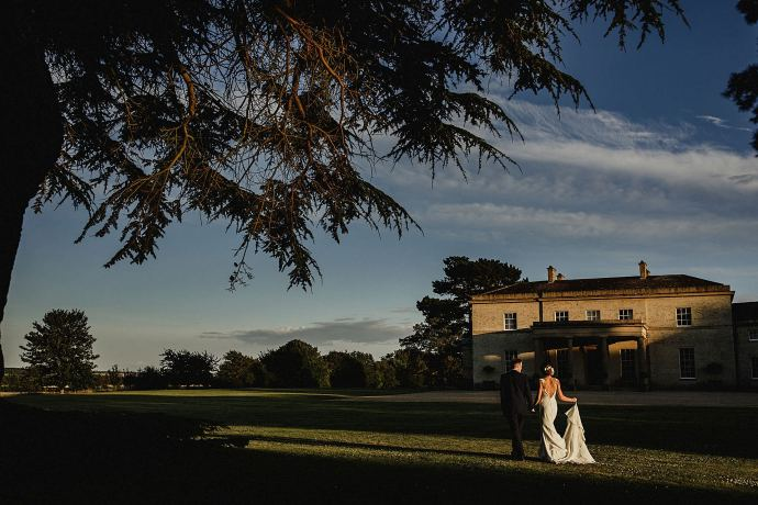 evening light wide portrait of the couple walking away from the hall