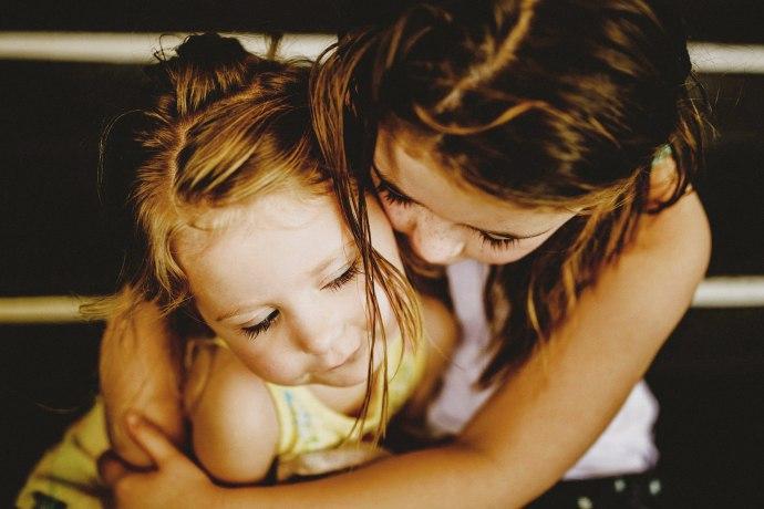 cuddling sisters