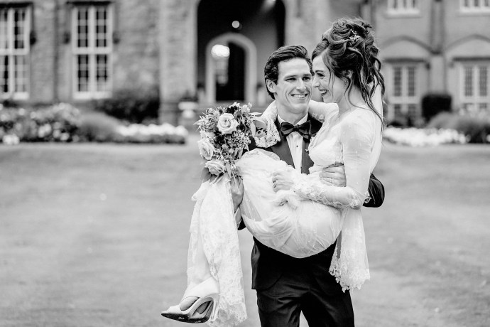 groom carrying the bride before wedding portraits on the lawn, wedding shoes,